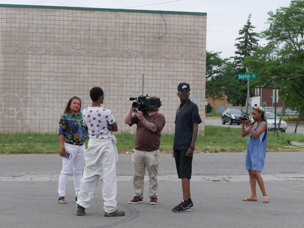 An image of people talking in a city parking lot. Geri is off to the left, listening intently while she talks with two men. There are two people filming the moment close up.