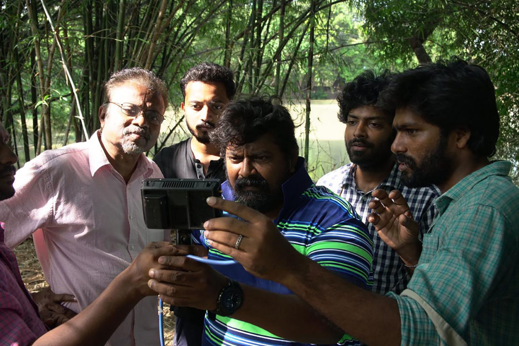 Swarnavel and others stand around a camera in what looks like a wooded area.